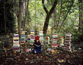 child with piles of books forest